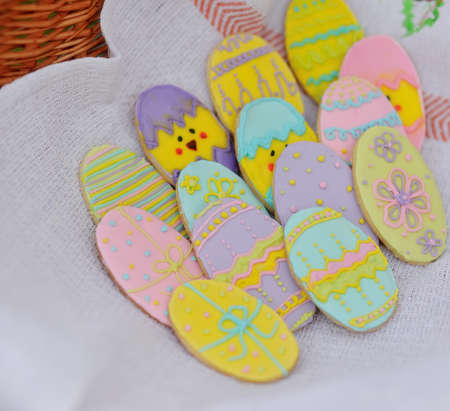 in basket on linen towel cookies in the form of Easter eggs photo