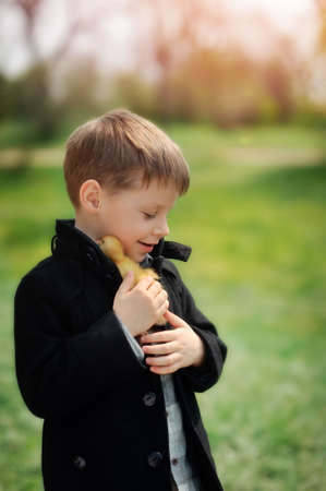 yellow duckling: on the nature of the boy in a black coat plays with yellow duckling