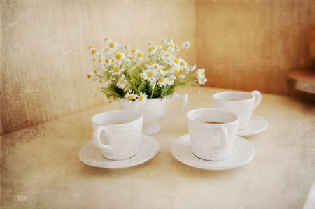 beautiful table setting of white cups of tea and white vase bouquet of daisies photo