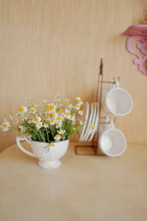 on a beige background white cup on a stand, and one with a bouquet of daisies photo