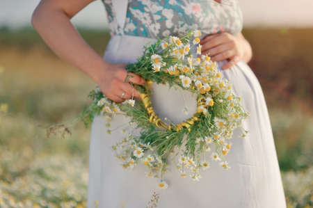 against the background of the field of chamomile belly of a pregnant woman with a wreath of daisies in her hand photo