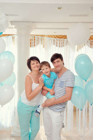 happy family in turquoise costumes against the backdrop of balloons