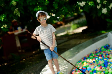 little boy in a cap and sunglasses collects a net colored balls photo