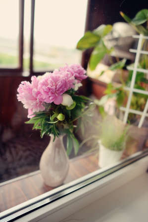 on the windowsill in a beautiful vase of lush bouquet of peonies and vase with green grass photo