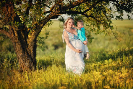 Outdoors under a tree is a pregnant woman with a young son in her arms photo