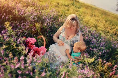 Summer walk on the field with wildflowers pregnant mother with a young son photo