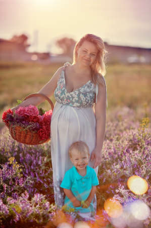 Summer walk on the field with wildflowers pregnant mother with a young son Stock fotó - 20295864