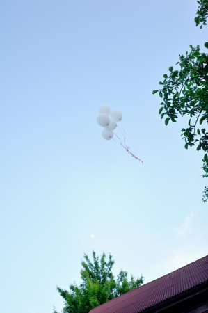 high in the sky flying a bunch of white balloons photo