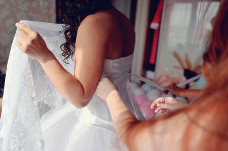the bride wearing a wedding dress and lace up corset photo