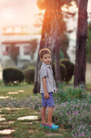 little boy walks in the park outdoors in the sun photo