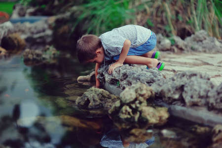 the stream boy plays in the water and beautiful reflection in the water photo