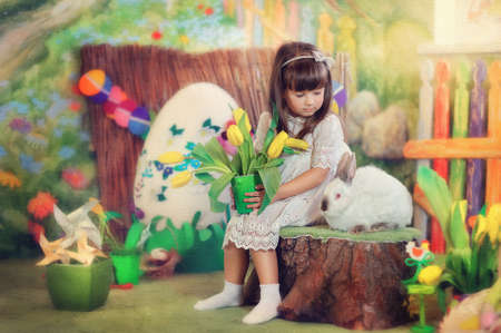 Easter composition of a little girl in a white dress with a rabbit and flowers photo