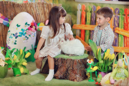 a fabulous farm boy and girl playing with white rabbit Stock fotó