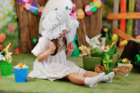 sitting on the floor of the Easter decorations lovely girl in a white dress and hat photo
