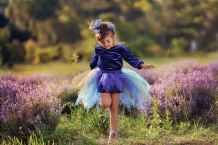 on the fragrant lavender walks beautiful girl in a smart dress photo