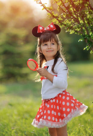 in the park on the lawn plays a girl in a suit of Mickey Mouse Stock Photo