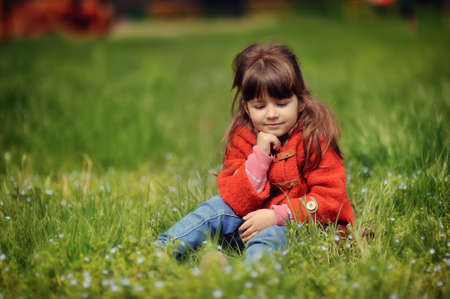 little girl in a red sweater with long hair resting on the grass photo