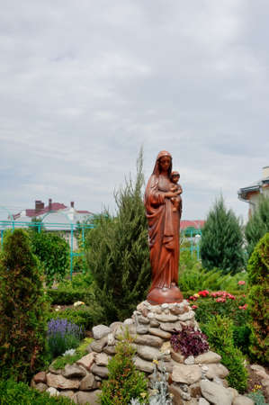 in the courtyard of the monastery in the flower garden is a large statue of the Virgin and Child photo