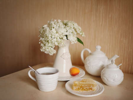 Still white crockery with honey in the comb, and a vase of white flowers photo