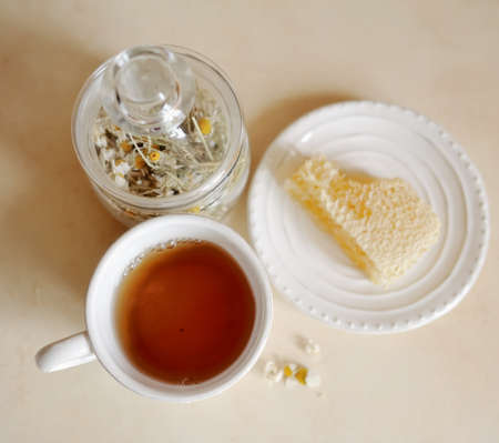 Honey in the comb on a white plate with a cup of tea with chamomile and bank photo