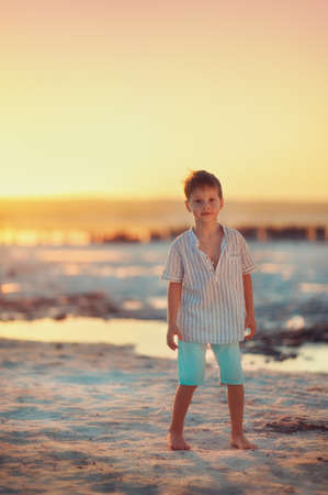 little boy stands barefoot at sunset on the sea photo