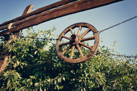 covered wagon: on the fence on chains hanging wooden wagon wheel