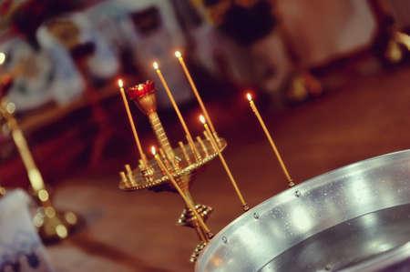 nella chiesa su uno sfondo di luci candelabro con candele e dei font