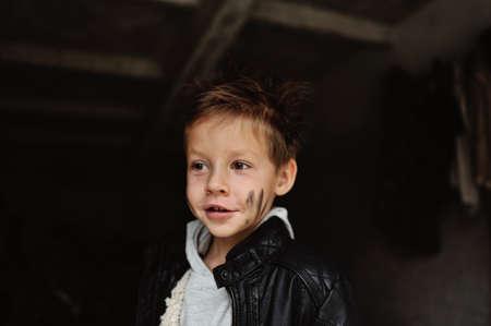 Retrato de un niño travieso con la cara sucia en una chaqueta negro Foto de archivo - 22279101