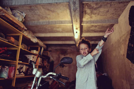 in the garage of a boy in jacket with a dirty face on a moped photo