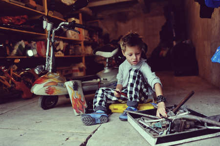 in the garage of a boy with dirty face and stylish hairstyle repairs moped photo