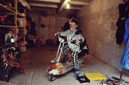 in the garage of a boy with dirty face and stylish hairstyle on a moped photo