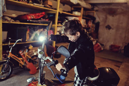 in the garage of a boy in a black jacket with a dirty face on a moped photo