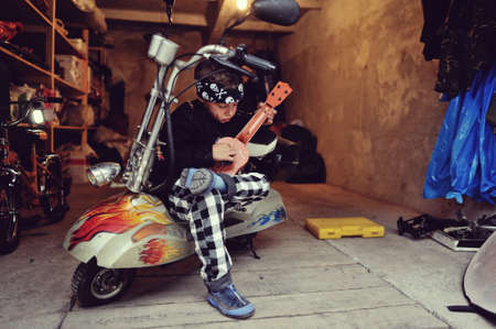 in the garage of a boy with dirty face and a moped with a guitar photo