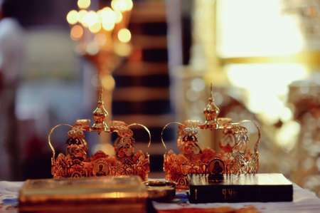 accessories for wedding in a church on a background of lights bible and two crowns photo