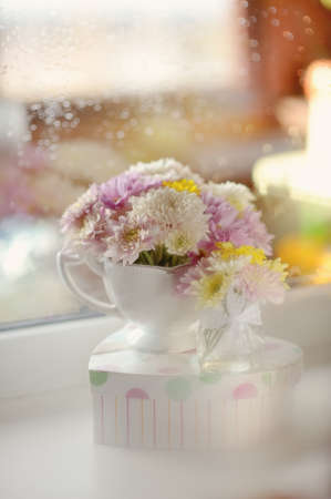 on the windowsill in a wet glass is white vase with a bouquet of flowers photo