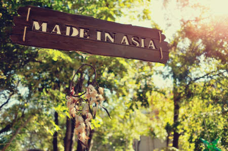 the sun among the foliage of trees wooden sign with the words, Made in Asia photo