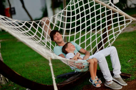 summer green park father and son are in a large hammock photo