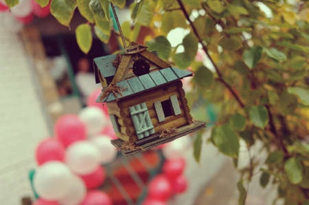 against the of balloons hanging from a tree a beautiful wooden house for the birds