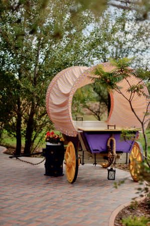 in the park is a wooden cart with pink flowers and a canopy photo