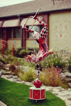 harlequin clown in disguise: on the green grass near the house bright clown doll clown doll