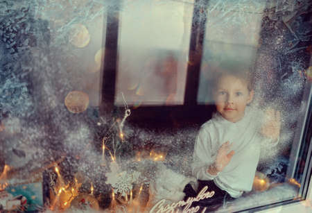 peeking: window with a winter pattern sitting little boy Stock Photo
