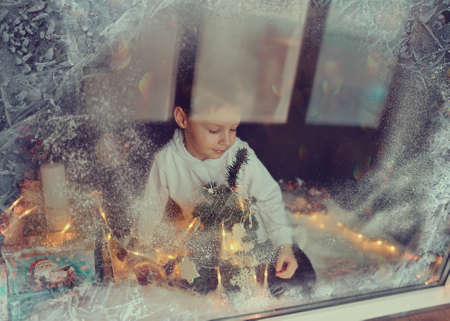 window with a winter pattern sitting little boy Stock Photo