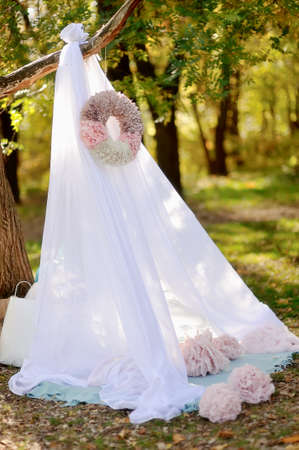 weighs: in the park on the tree canopy and weighs white paper wreath Stock Photo