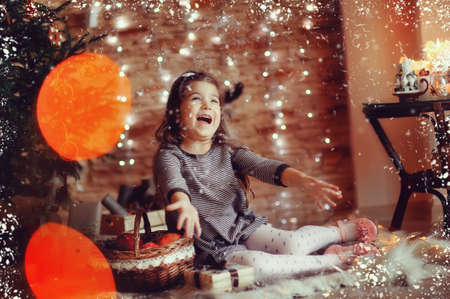 Christmas tree with toys and lights and happy cute little girl Stock Photo - 24469146