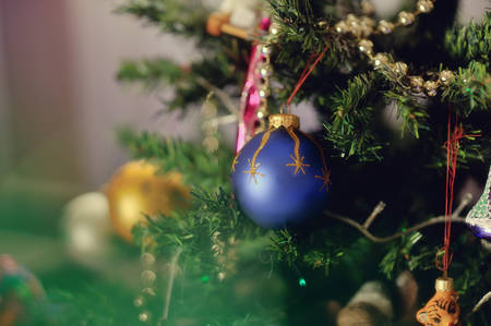 against the backdrop of a Christmas tree decorated with toys hanging beautiful blue ball