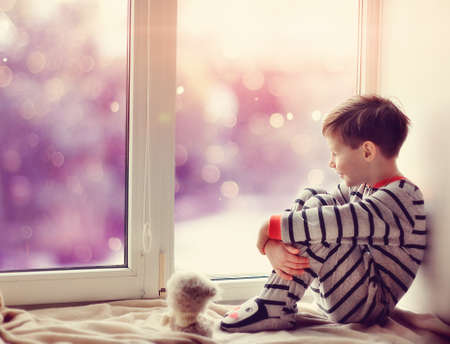 cute little boy sitting on the windowsill in the winter window photo
