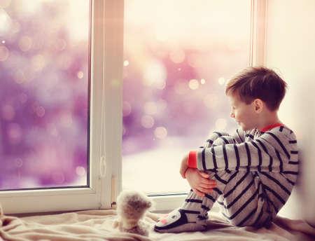 schattige kleine jongen zittend op de vensterbank in de winter venster Stockfoto