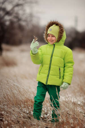 baby 4 5 years: boy in a green suit walks in the park in winter with frozen trees and grass Stock Photo