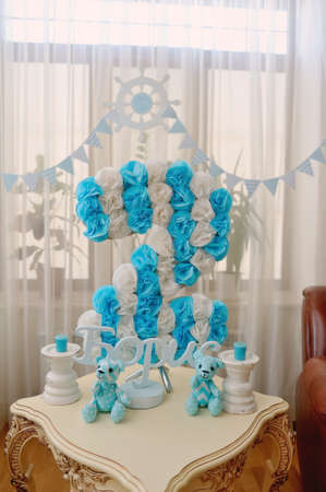 festive decoration in blue and white colors of paper flowers, candles and toy bear