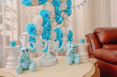 child s block: festive decoration in blue and white colors of paper flowers, candles and toy bear